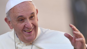Pope Francis smiles as he arrives to lead  weekly audience in St. Peter's Square at Vatican