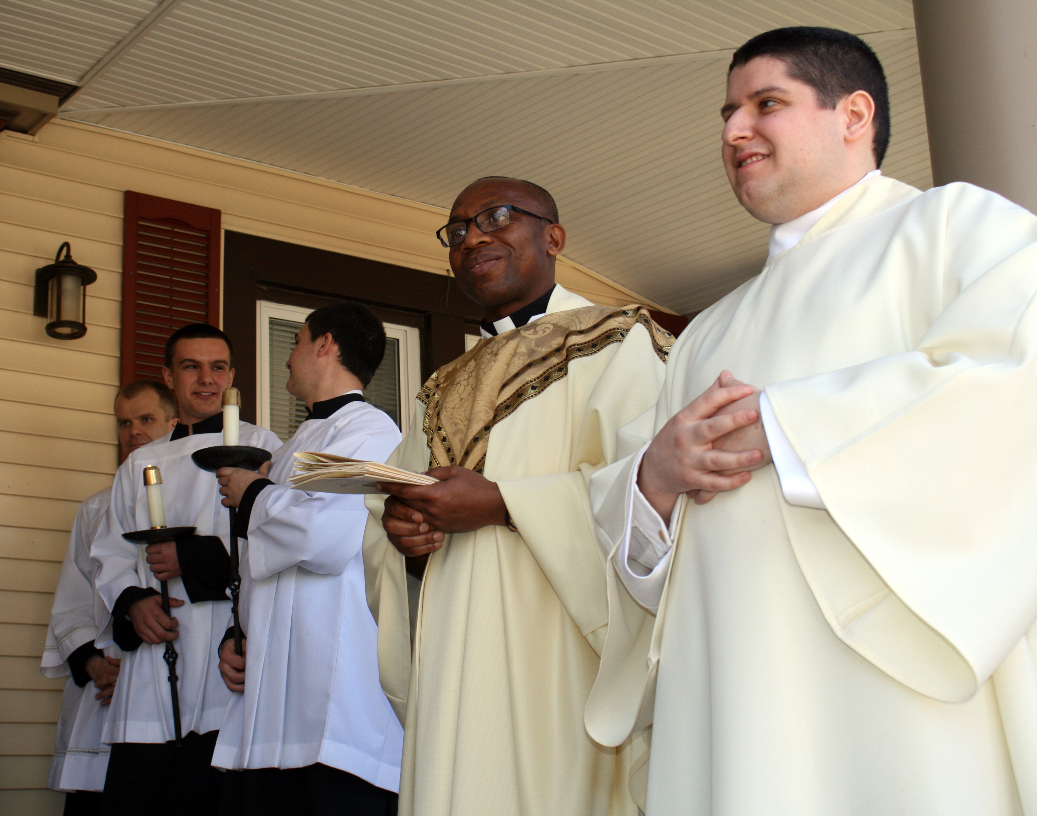 priests-servers-and-decon-on-porch-of-parish-center_0